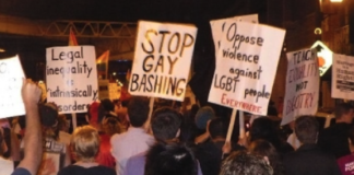 This image is from the article; it shows people holding signs demanding rights for the diverse SOGIESC community
