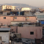 The image, from the cover of the report, is a close-up of dense housing. Some of the houses have satellite dishes and clothes drying on a line.